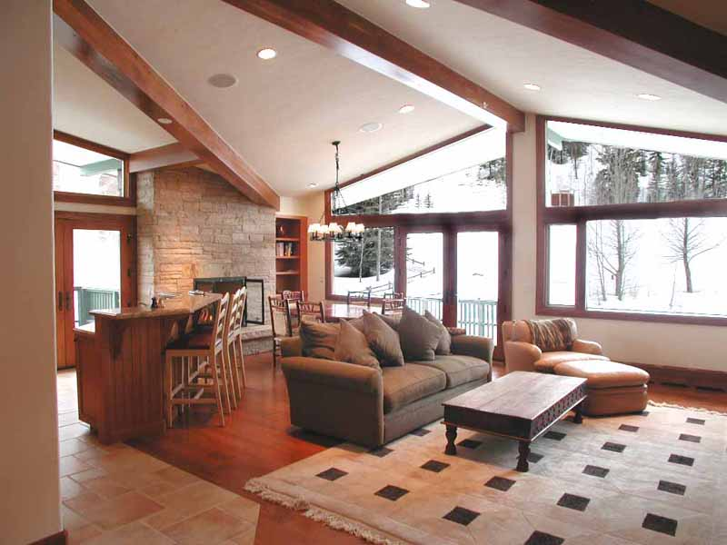 This is a view of the great room from the entry.  Some of the ski trails of Vail Mouintain are visible through the windows.  The unit has been updated with new American Cherry floors, all new cabinetry and new windows.  The walls feature new insulation and drywall.