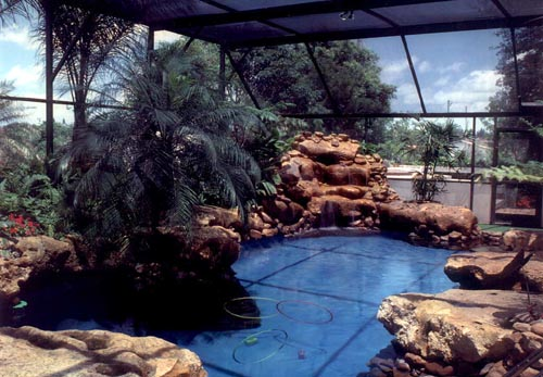 Boulders were added to the existing rectangular pool along with a waterfall and landscaping to give it a lagoon like feel.