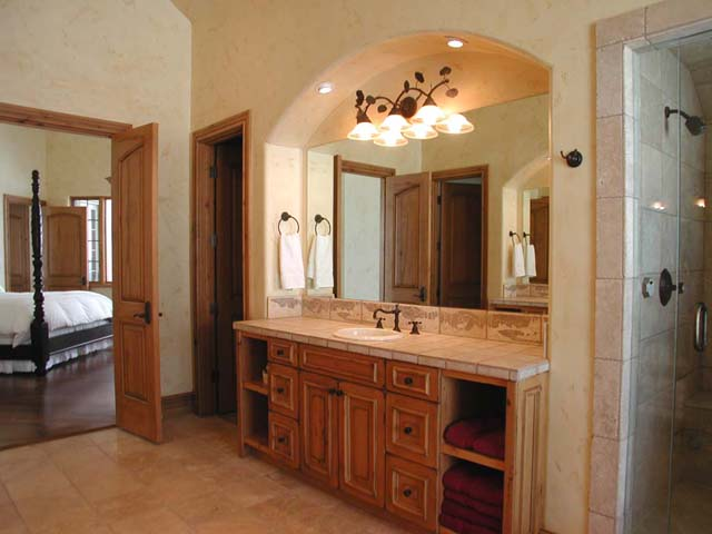 The master bathroom has two sinks in separate vanities, a generous jetted soaking tub, a steam shower, and is tiled with tumbled marble.
